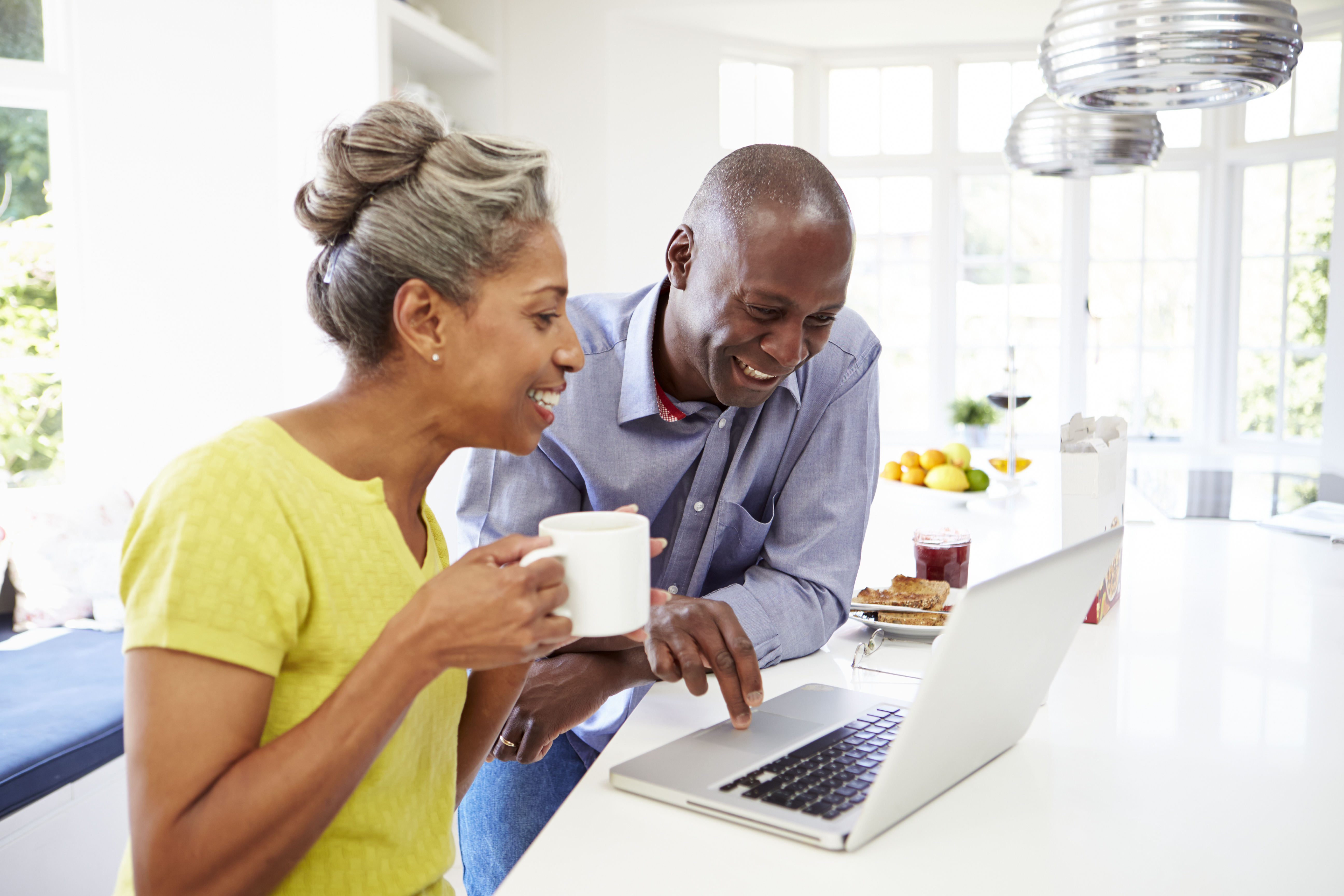 a middle aged couple using a computer